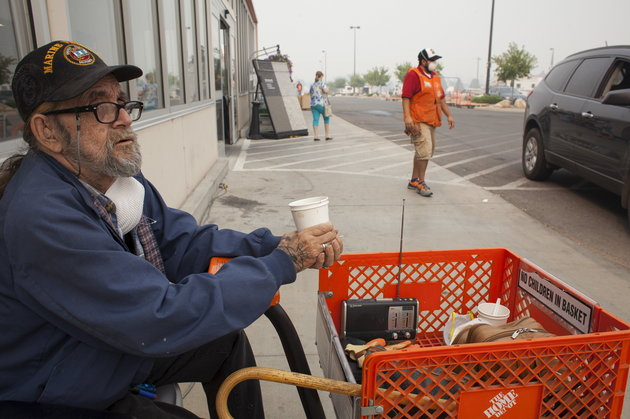 US Marine Corps veteran Martin Silverhawk sits outside a Home Depot store, where he has been living since evacuating his home, during the Okanogan Complex fire in Omak, Washington